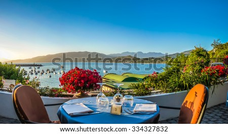Romantic dinner place with idyllic panoramic view of mediterranean coastal landscape at sunset in golden evening light - stock photo