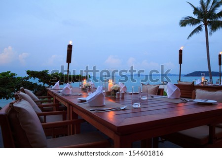 Romantic dinner setting at the beach on sunset, outdoor restaurant tables - stock photo