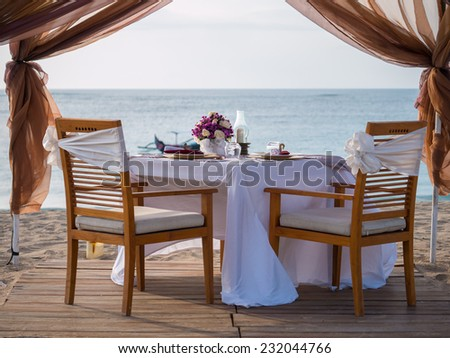 Romantic dinner setting on the beach - stock photo