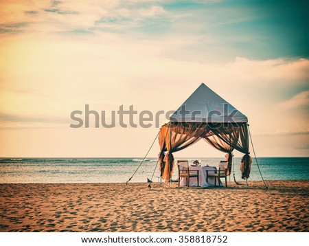 Romantic dinner setting on the beach at sunset - stock photo