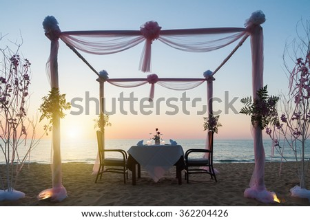 romantic dinner setup ,on the beach with sunset - stock photo