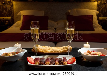 romantic dinner with champagne in the bedroom - stock photo