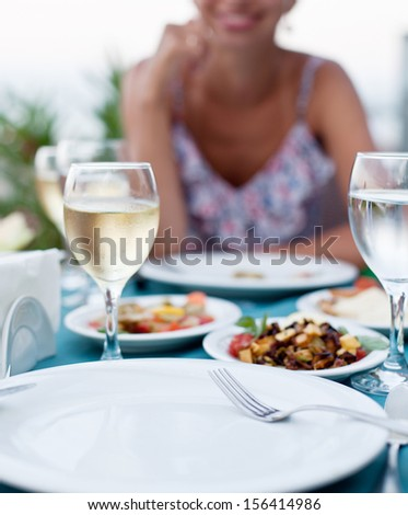 Romantic dinner with white wine. In the background a girl is out of focus.