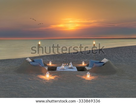 Romantic dinner with wine, candles and torches at ocean beach during wonderful sunset and flying birds couple. Honeymoon, proposal or wedding background concept. - stock photo