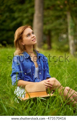 Romantic dreamer young woman sitting on the grass and looking up. Summer season.