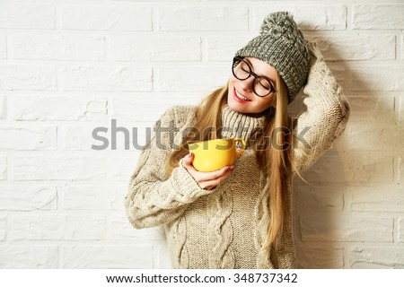 Romantic Dreaming Hipster Girl in Knitted Sweater and Beanie Hat with a Mug in Hands at White Brick Wall Background. Winter Warming Up Concept. - stock photo