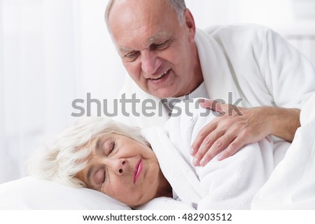 Romantic elder couple in bed- husband observing sleeping wife