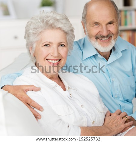 Romantic elderly couple sitting close together on a sofa in their living room in a loving embrace smiling at the camera - stock photo