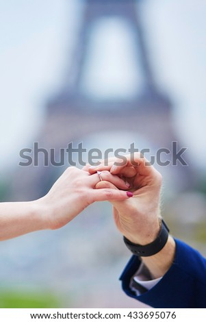 Romantic engagement in Paris, man proposing to his girlfriend near the Eiffel tower. Surprise proposal or elopement concept - stock photo