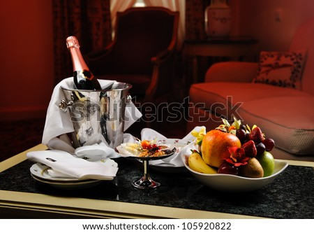 Romantic evening with bottle of champagne, sweets and fruits in the hotel room - stock photo