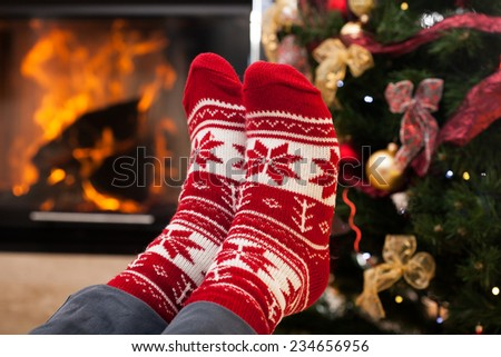 Romantic feet warming by the hot fireplace - stock photo