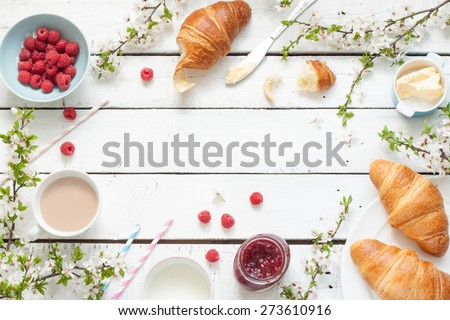 Romantic french or rural breakfast - cocoa, milk, croissants, jam, butter and raspberries on rustic white wood table from above. Countryside weekend morning concept. Background with free text space. - stock photo