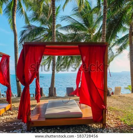 Romantic gazebo lounge at tropical resort. Beach beds among palm trees. - stock photo