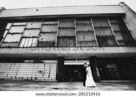 romantic gentle stylish bride and groom on the background  abandoned industrial building