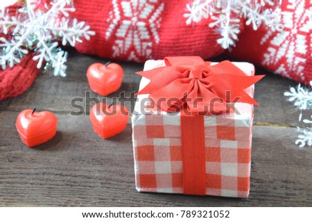 Romantic gift with candles on wooden background. Love concept. gift wrapped with a red bow, candles in the shape of a heart, on a background of scarf, rope, snowflakes. St. Valentine's Day