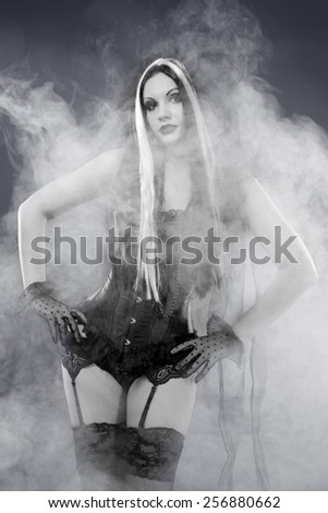 Romantic gothic girl in corset, shot over smoky background - stock photo
