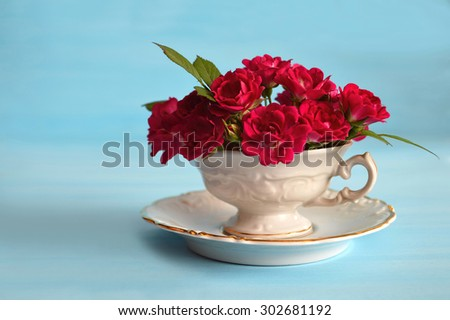 Romantic greeting card: Roses in tea cup on blue background - stock photo