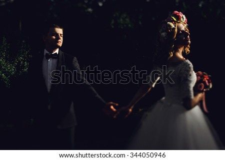 Romantic handsome groom in suit holding hands with gorgeous young bride at sunset in park - stock photo