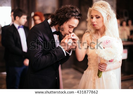 Romantic handsome groom kissing beautiful bride's hand at wedding ceremony - stock photo
