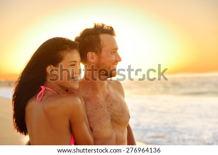 Romantic happy couple lovers on beach honeymoon having playful fun together during summer beach holidays. Cheerful young multiracial couple, Asian woman and Caucasian man. From Oahu, Hawaii, USA. - stock photo