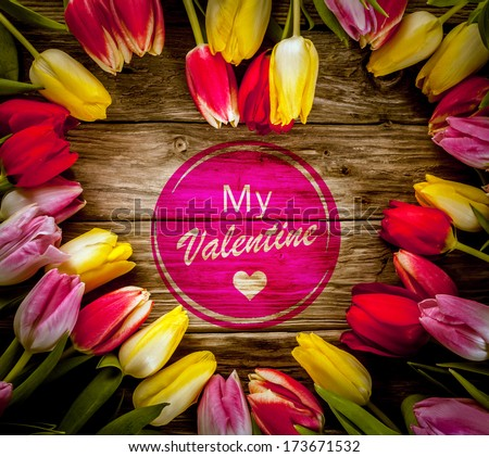 Romantic heart-shaped colourful tulip frame made of fresh flowers on a rustic wooden background for Valentines Day with a central - My Valentine - wish - stock photo