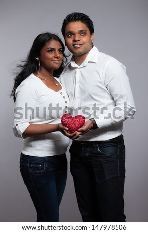 Romantic indian couple holding red heart. Wearing white shirt and jeans. Studio shot against grey.