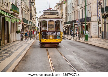 Romantic Lisbon street with the typical yellow tram and Lisbon street on the background