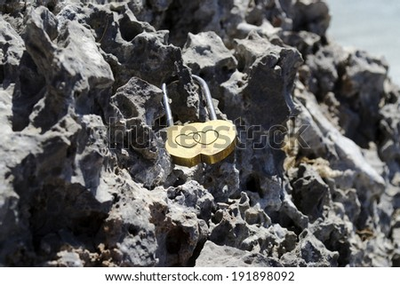 Romantic love lock in shape of heart hitched to the rock - stock photo