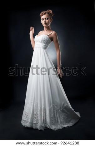 Romantic lovely bride fashion model female demonstrates white wedding dress on podium - stock photo