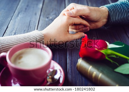 Romantic lovers dating. Male and female hands caressing with love. Couple on secret dating at coffee shop. - stock photo