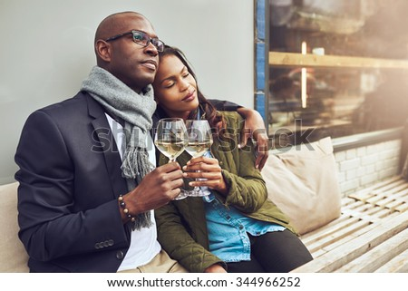 Romantic loving couple enjoying each others company sitting relaxing on a wooden restaurant bench in a close embrace drinking white wine - stock photo