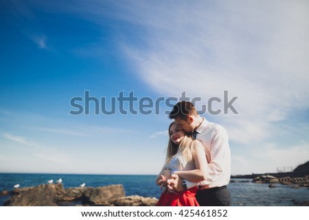 Romantic loving couple posing on stones near sea, blue sky