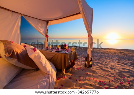 Romantic luxury dinner setting at tropical beach on sunset - stock photo