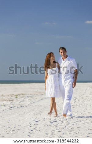 Romantic man and woman romantic couple in white clothes walking on a deserted tropical beach with bright clear blue sky - stock photo