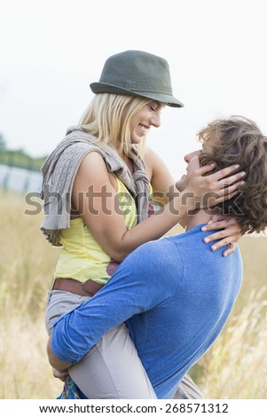 Romantic man carrying woman in field - stock photo