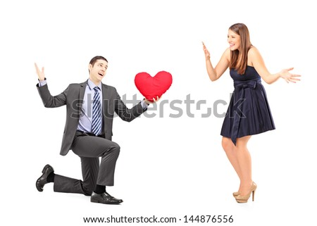 Romantic man giving a red heart to a young woman, isolated on white background - stock photo