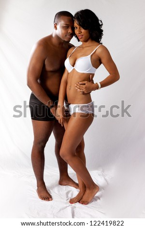 Romantic married Black couple in their underwear, standing in a tender, romantic mood and touching each other - stock photo