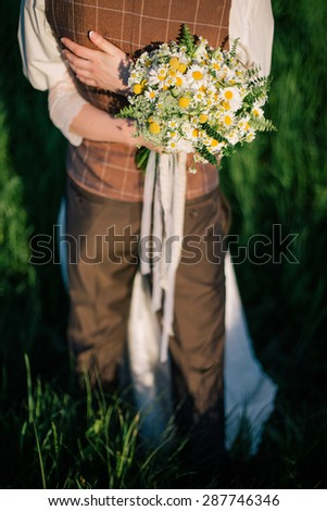 Romantic Married Couple. Brides hands with bouquet hugging groom - stock photo