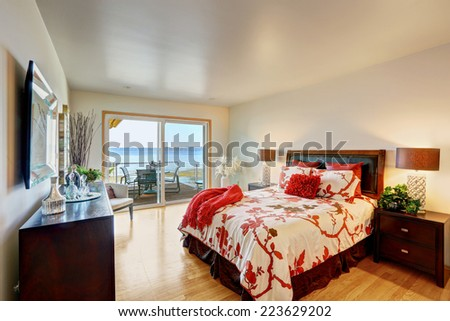 Romantic master bedroom interior with walkout deck. Bed with white and red bedding, decorated with pillows - stock photo