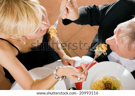Romantic mature couple having dinner feeding each other with pasta in a fancy restaurant - stock photo
