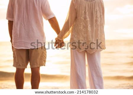 Romantic Mature Couple Holding Hands Enjoying at Sunset on the Beach - stock photo