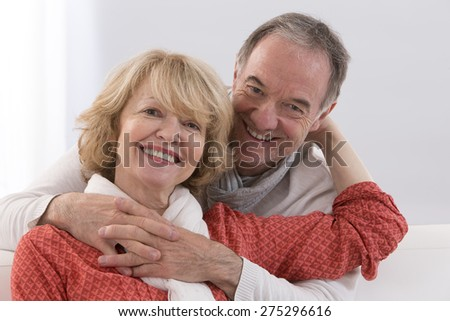 Romantic Mature couple sitting close together on a sofa in their living room in a loving embrace smiling at the camera - stock photo