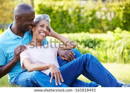 Romantic Mature Couple Sitting In Garden - stock photo