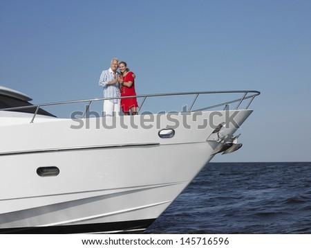 Romantic middle aged couple enjoying drinks on yacht - stock photo