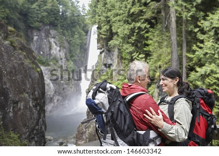 Romantic middle aged man and woman with backpacks against waterfall - stock photo