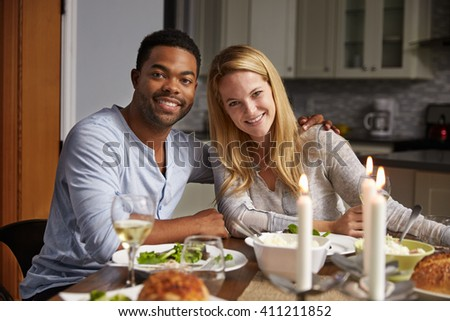 Romantic mixed race couple look to camera at meal in kitchen - stock photo