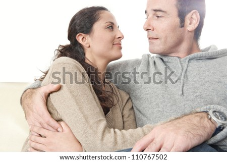 Romantic moment of a hispanic couple sitting down on a while leather sofa at home. - stock photo