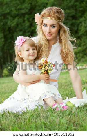 Romantic mother and baby girl sitting on grass