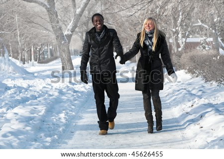 Romantic multi-etnic couple is walking in the winter park - stock photo