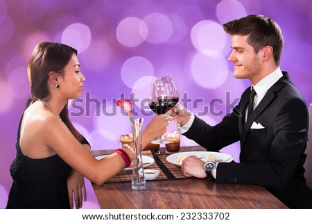 Romantic multiethnic couple toasting wineglasses at restaurant table - stock photo